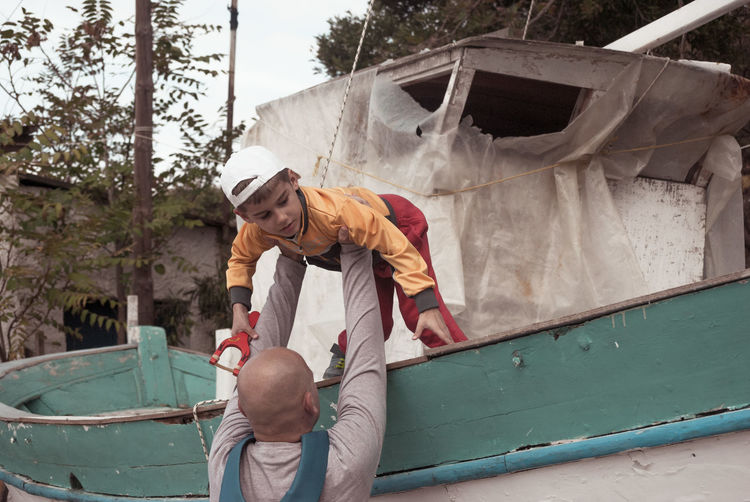 Rear View Of Man Putting Boy On Boat