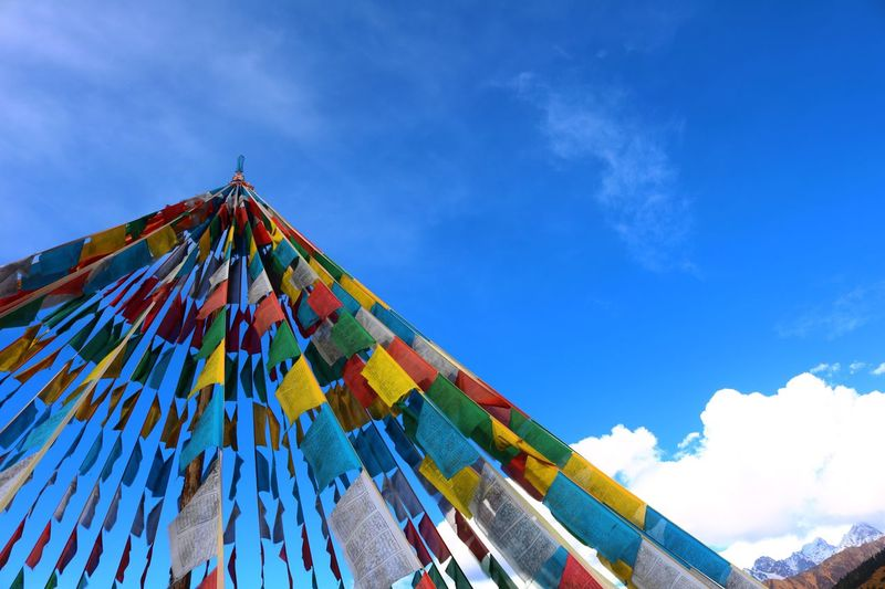 Low Angle View Of Colorful Prayer Flags Against Blue Sky