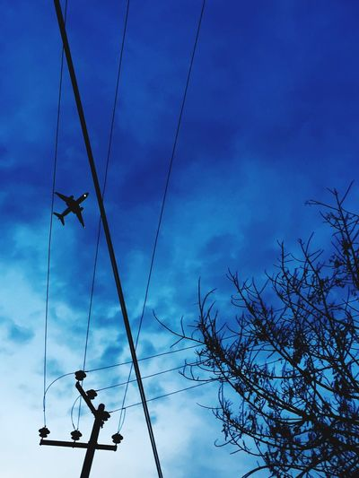 Low Angle View Of Airplane Flying Over Power Line Against Blue Sky At Dusk
