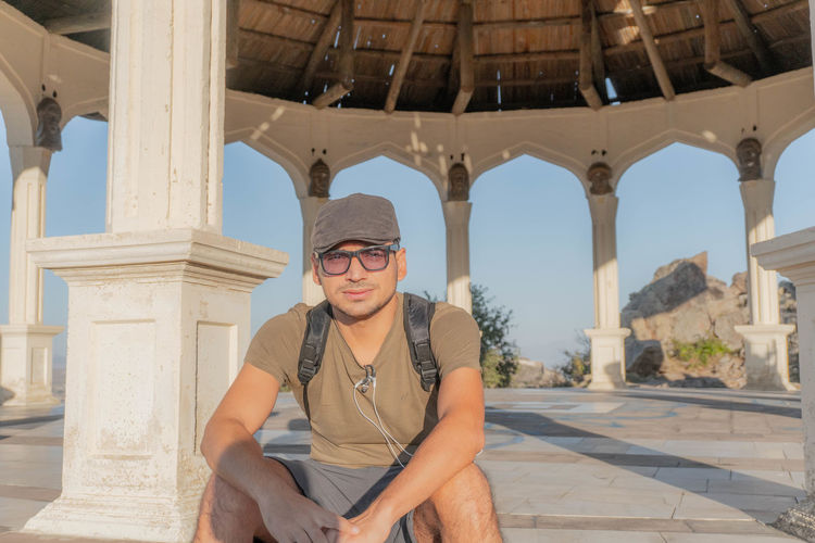 Portrait of man wearing sunglasses while siting in gazebo