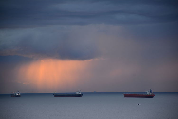 Ships in sea against sky during sunset