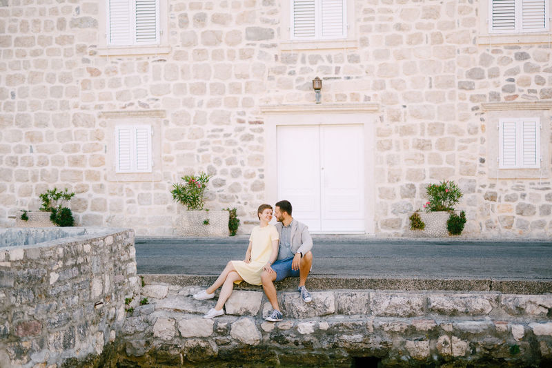 Full length of couple sitting against building
