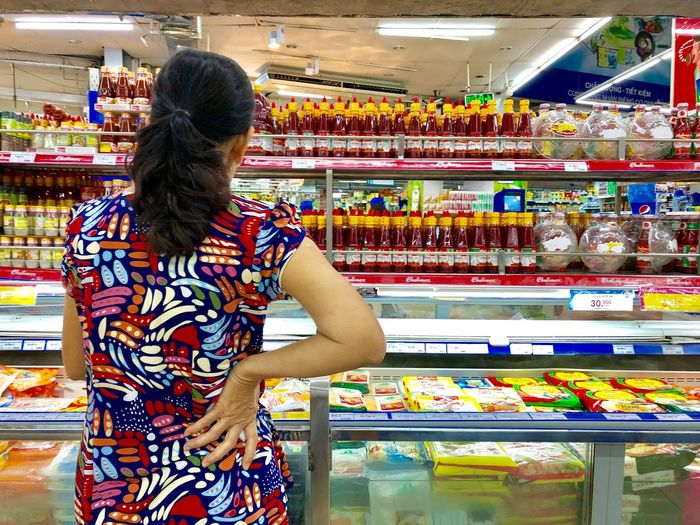Retail  One Person Adult Women Store Rear View Supermarket Shopping Three Quarter Length Choice Buying Real People Food And Drink Standing Decisions Multi Colored Arrangement Casual Clothing Consumerism Variation