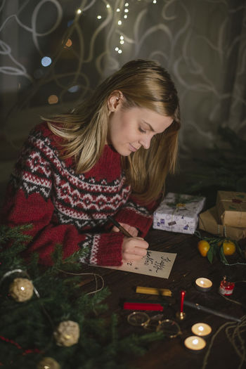 Woman writing in book by christmas tree at home