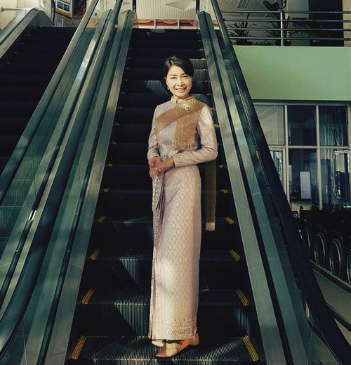 Portrait of woman in traditional clothes while standing on escalator