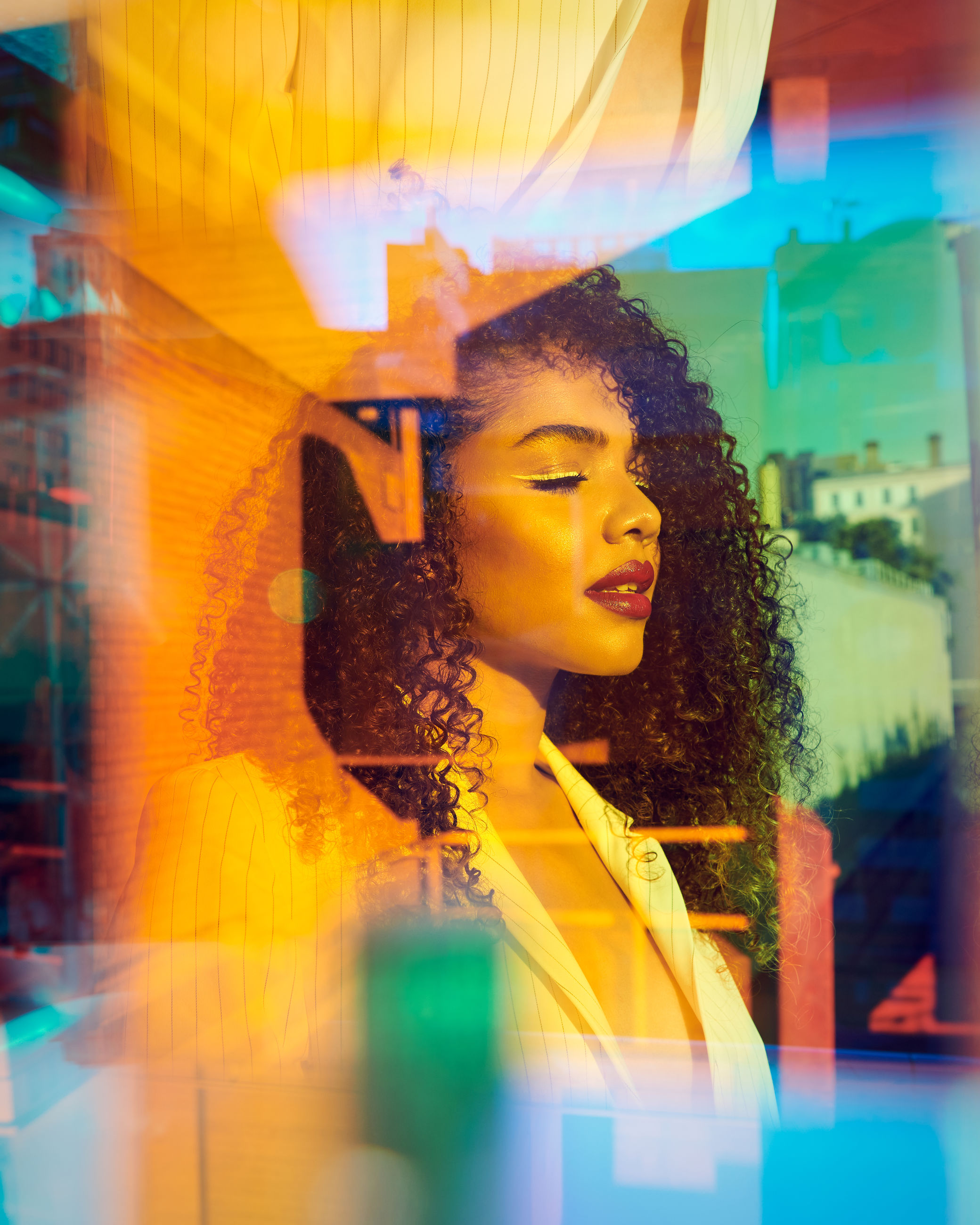 glass - material, young adult, window, one person, looking, store, real people, transparent, portrait, indoors, retail, looking away, human representation, store window, selective focus, lifestyles, curly hair, hairstyle, reflection, digital composite, contemplation, retail display, beautiful woman, consumerism