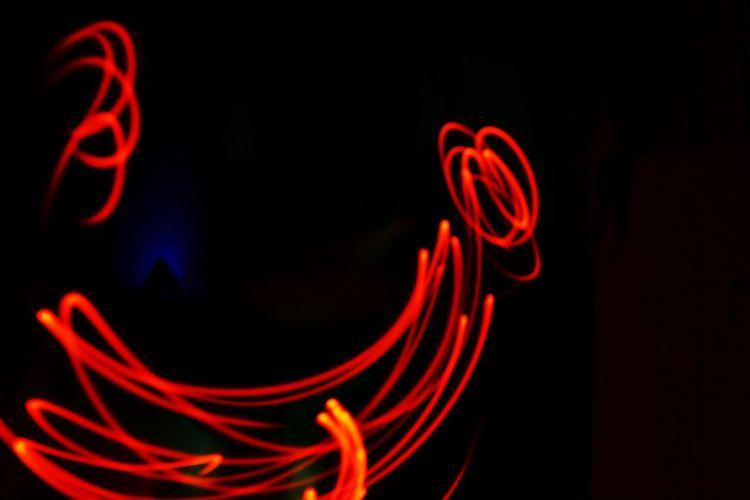Close-up of illuminated red light against black background