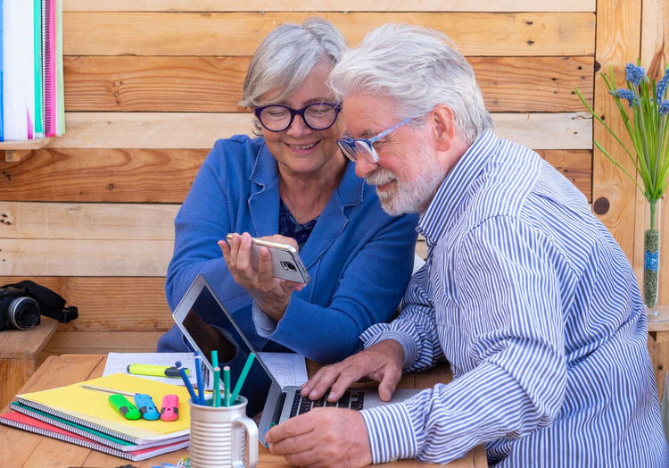 Senior couple using laptop and digital tablet while sitting on table