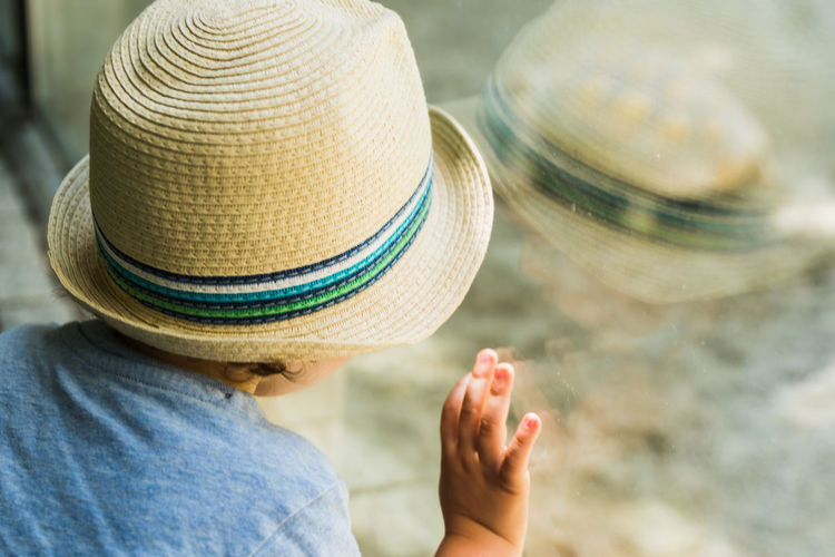 Close-up of boy with hat looking through window