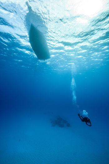 Scuba diver swimming below boat undersea