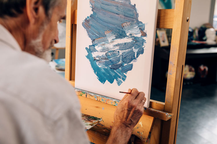 Rear view of senior man painting in workshop