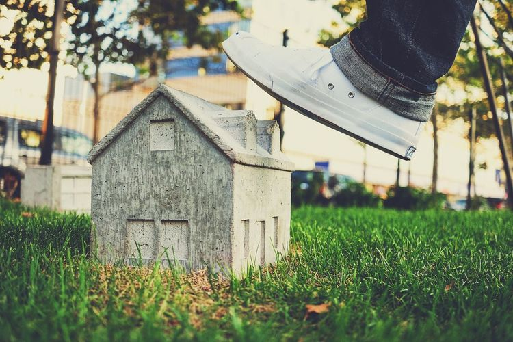 Cropped Image Of Leg Stepping On House Model In Yard