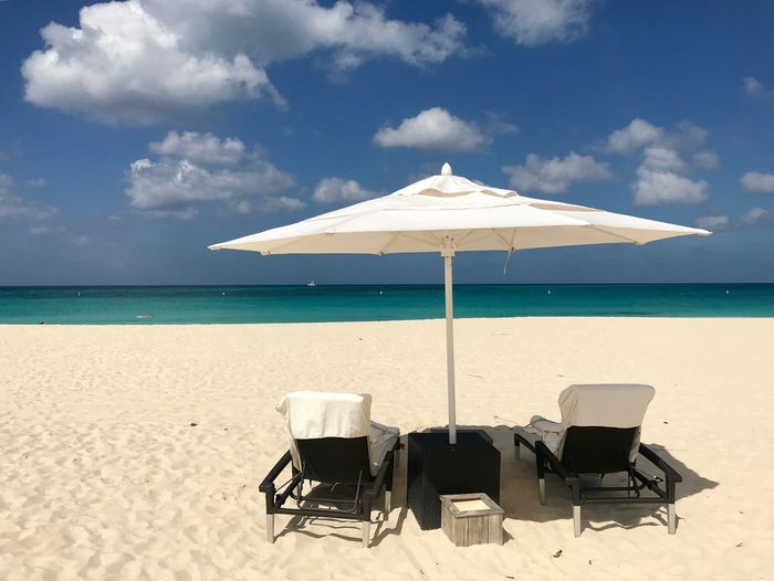 Tropical Paradise White Sand Sunbeds And Umbrella Aruba Landscape Travel Relaxation Leisure Antilles Caribbean Beach Sand Sea Sky Beauty In Nature Water Nature Chair Horizon Over Water Tranquility Absence Sunlight Tranquil Scene Cloud - Sky Outdoors Scenics Day Summer No People Vacations