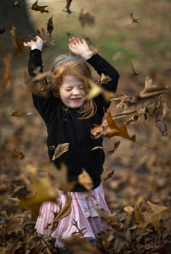 A five-year-old red head girl plays with leaves on a fall afternoon. Child Childhood Girls Females Real People Smiling Happiness Leisure Activity Human Arm Land One Person Front View Field Casual Clothing Lifestyles Autumn Emotion Innocence Arms Raised Outdoors Leaves Change Fall Leaf