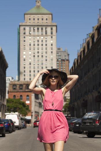 Full length portrait of woman on street in city