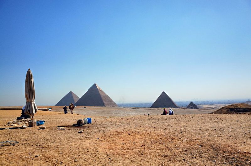 The Pyramids of Giza Landscape Desert Rock Formation The Past Stone Egypt Pyramids Of Giza Horizon Sky Land Clear Sky Sand Beach Scenics - Nature Nature Blue Day Incidental People Architecture Sunlight Built Structure Sunny Tranquility Pyramid Tranquil Scene Outdoors Travel Destinations History Environment Ancient