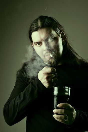 Portrait of man smoking against gray background