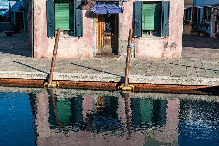 Reflection of residential building in canal water in burano, italy