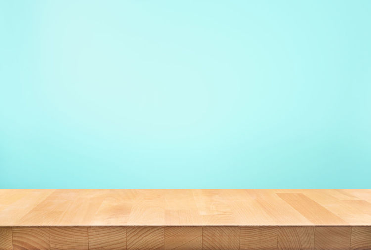 Close-up of wooden table against blue wall