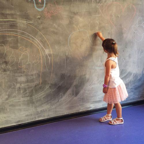 Full length of girl drawing on blackboard