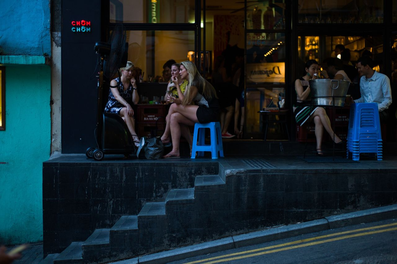 real people, steps, sitting, leisure activity, lifestyles, food and drink, outdoors, night, men, women, full length, architecture, friendship, people