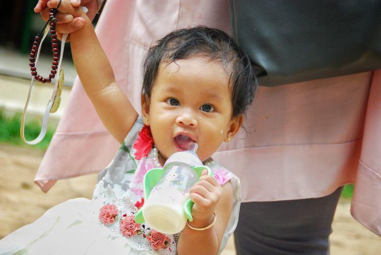 Portrait of cute baby girl holding milk bottle