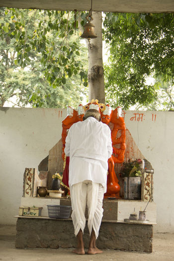 Rear view of man praying god in temple