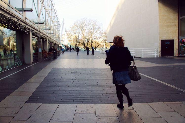 Rear view of woman walking on cobblestone street