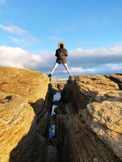Full length of man standing on rock formation against blue sky