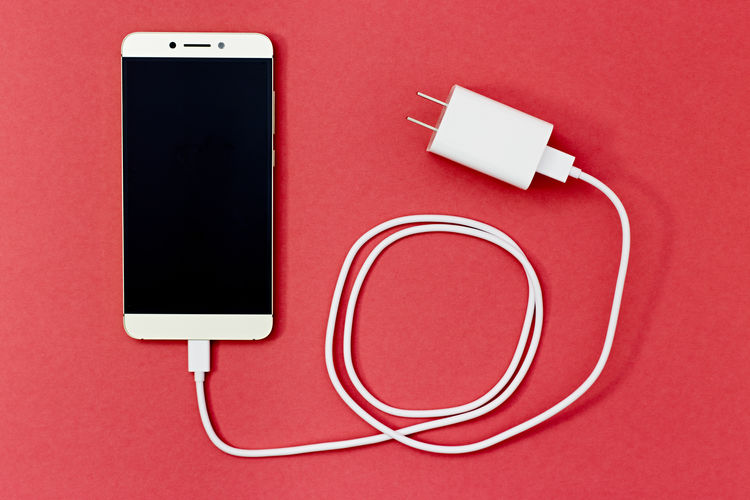 Cellphone/smartphone with attached charger, red background, photographed from above 3g 4g Plug Screen Black Cable Charger Close-up Communication Computer Connection Illustration Indoors  Mobile Phone No People Phone Portable Information Device Red Smart Phone Technology Telephone Wall Plug White Wireless Wireless Technology