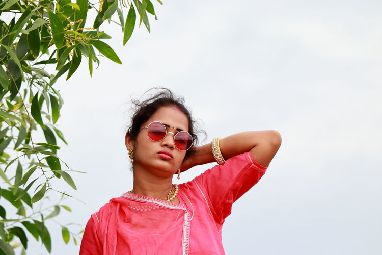 Portrait of young woman wearing sunglasses standing against sky