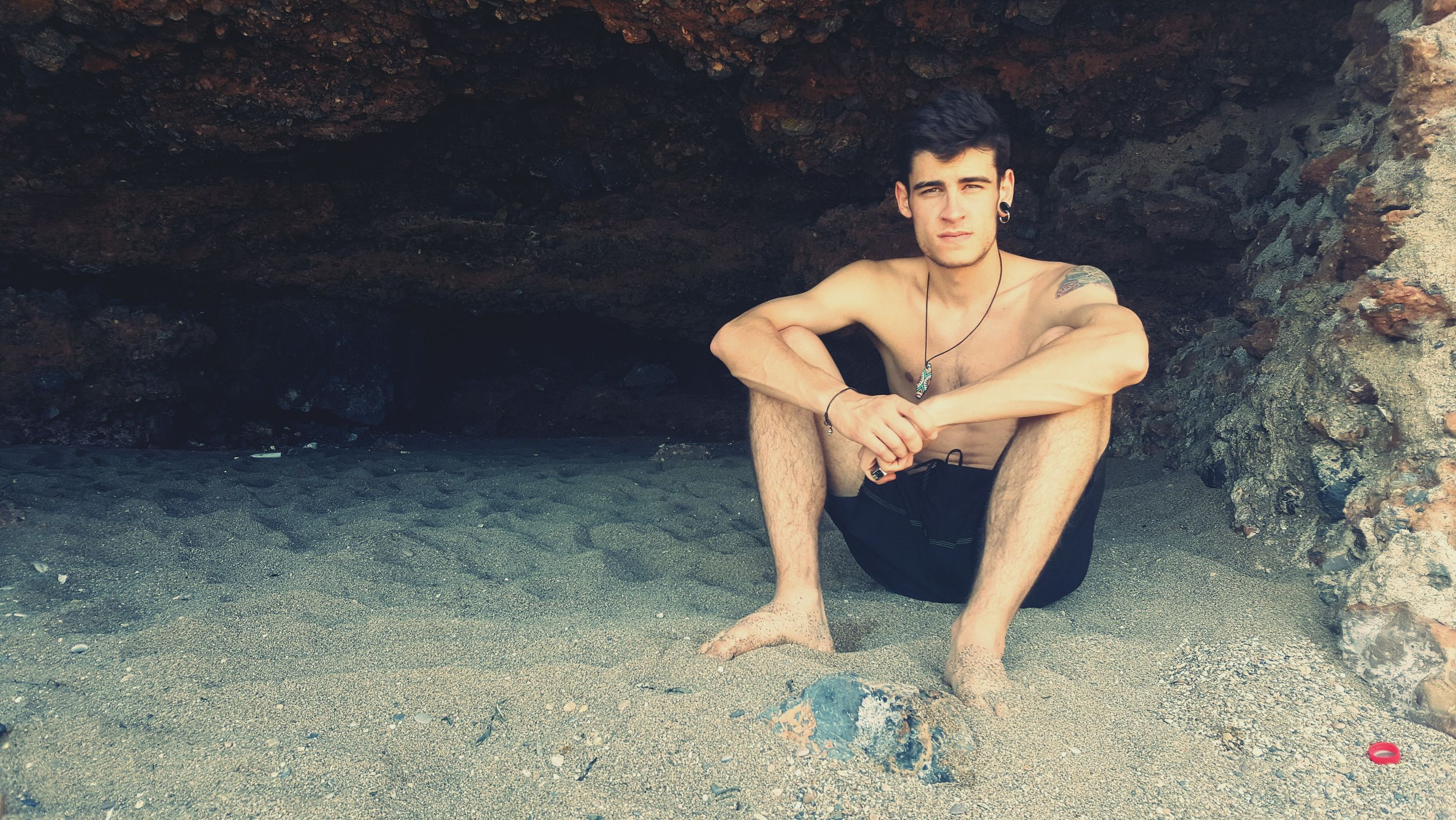 full length, young adult, rock - object, looking at camera, sitting, young men, real people, one person, portrait, front view, leisure activity, shirtless, day, young women, lifestyles, outdoors, water, nature, tree, people