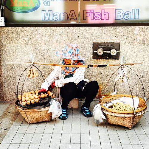 Man sitting in basket on floor against wall