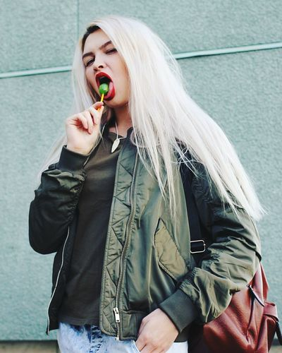 Portrait of young woman eating lollipop
