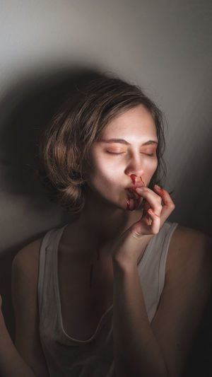 Portrait of young woman sucking your finger