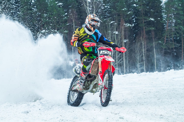 Man riding dirt bike on snow covered field