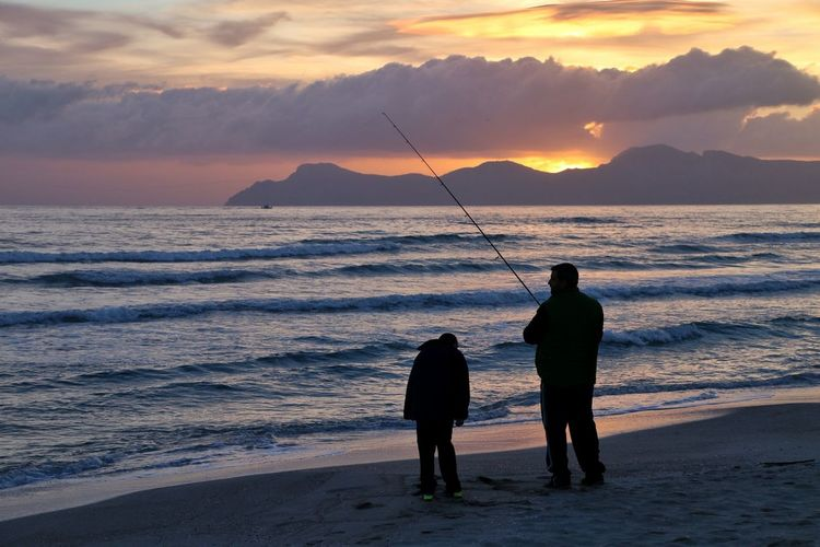 Rear view of silhouette man fishing at beach during sunset