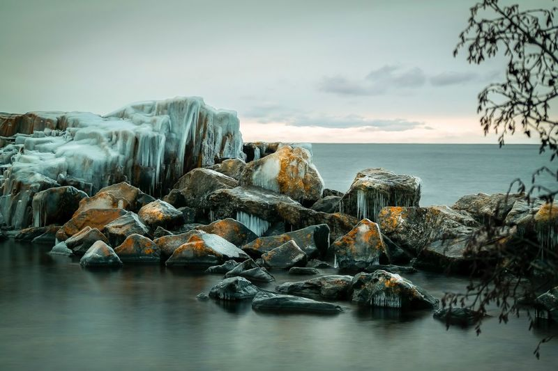 Frozen rocks in sea during winter