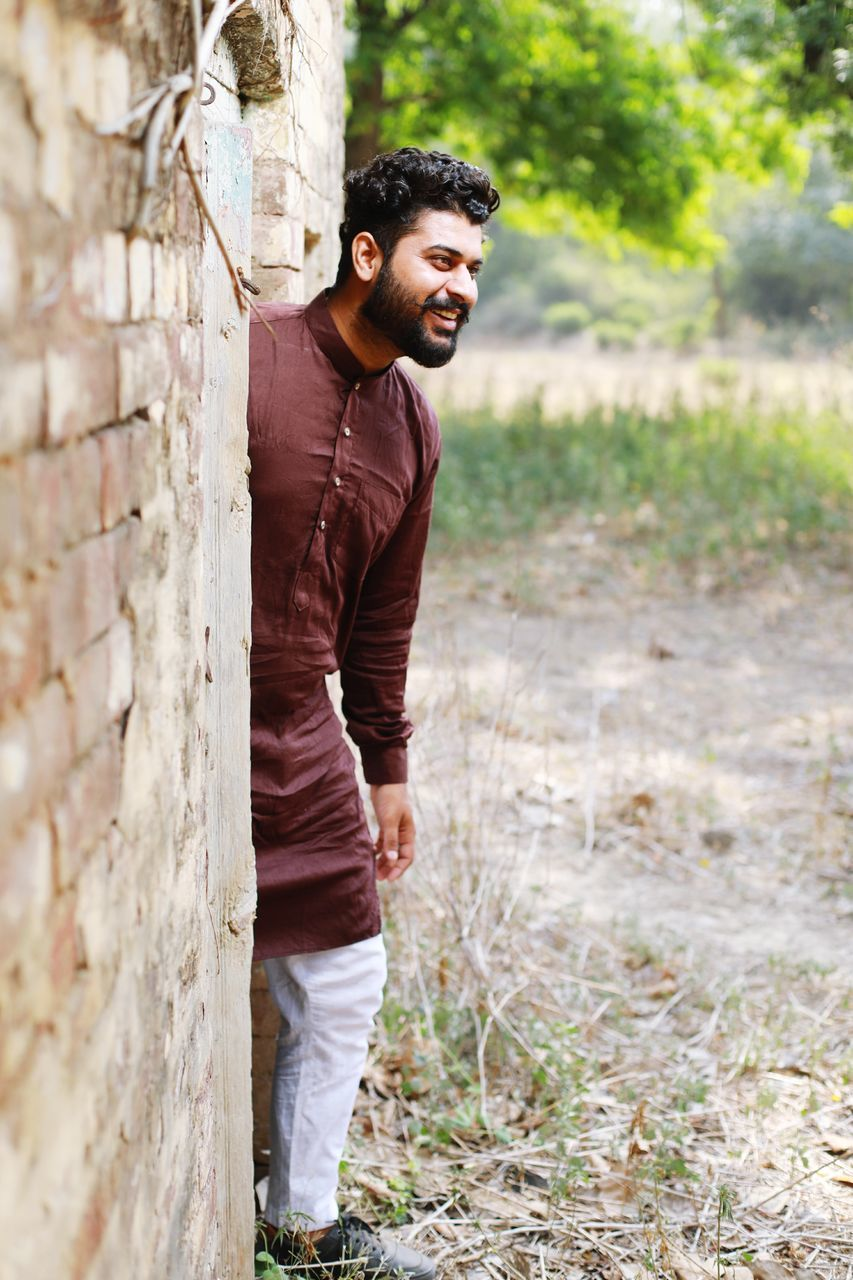 Smiling Young Man In Kurta Looking Away While Standing By Wall On Field