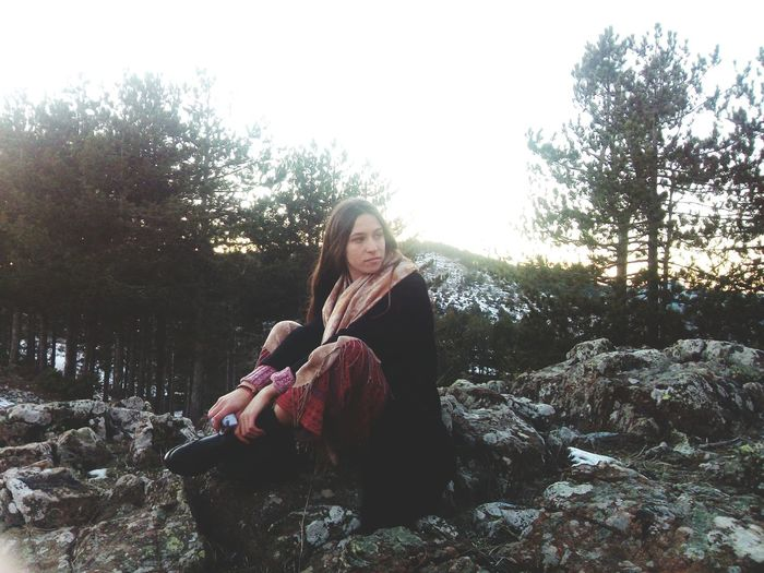Young woman sitting on rock against trees