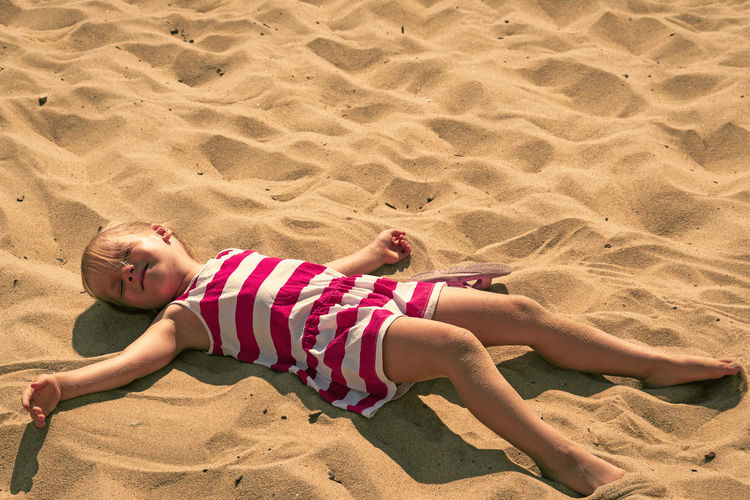 High angle view of girl lying on sand