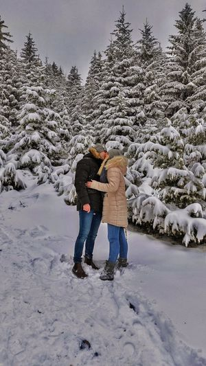 Full length of woman on snow covered tree