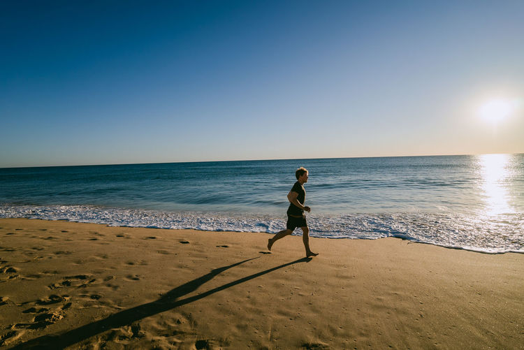 Full Length Of Man Running On Beach Against Clear Sky
