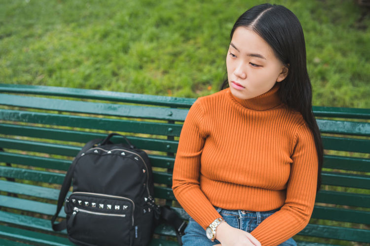 Thoughtful young woman sitting on bench