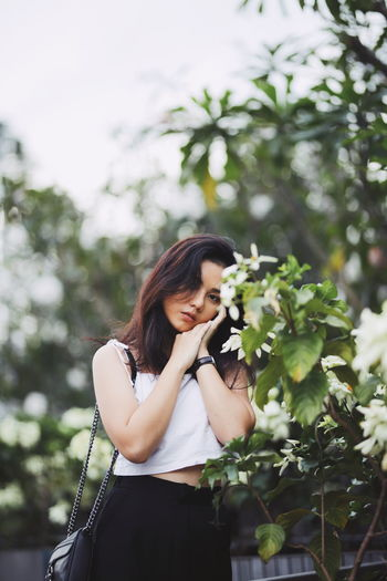 Portrait of beautiful woman standing by plants