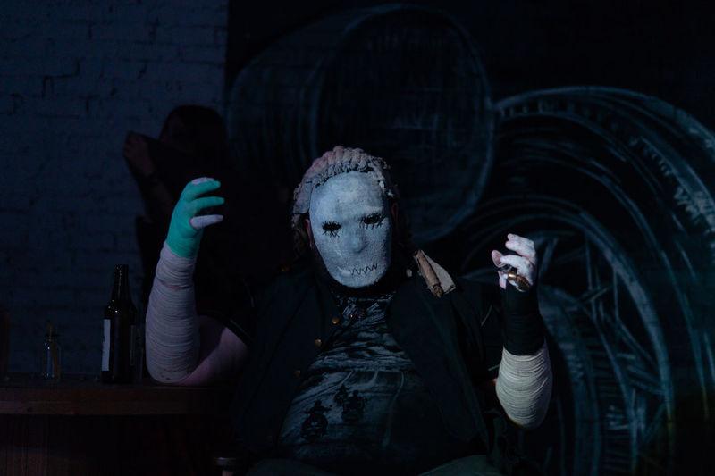 Man wearing halloween costumer sitting at table in darkroom