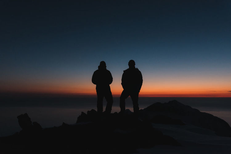 Silhouette men standing on rock by sea against sky during sunset