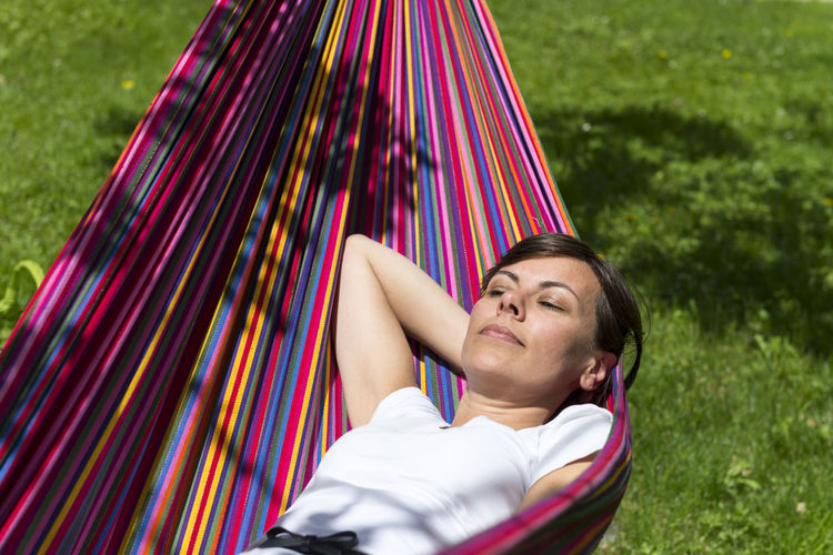 High Angle View Of Mature Woman Lying On Hammock During Sunny Day