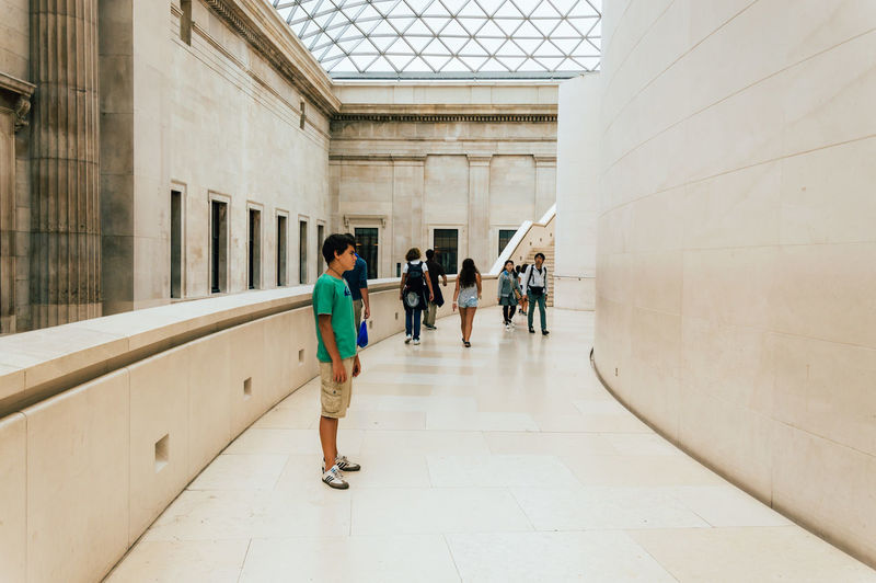 Young standing on the main hall of British Museum Architectural Column Architecture Building Built Structure City Life Corridor Cute Day Diminishing Perspective Education Full Length Leisure Activity Lifestyles London Men Museum Music Narrow Summer The Way Forward Tourist Traveling Walkway Young Adult