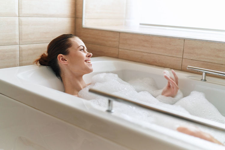 Smiling woman in bathtub